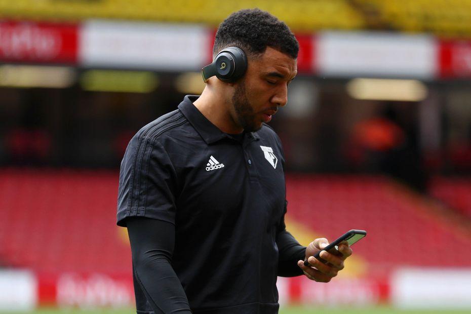 Troy Deeney looking at phones