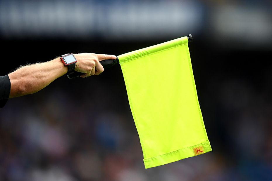 An assistant referee flags for offside