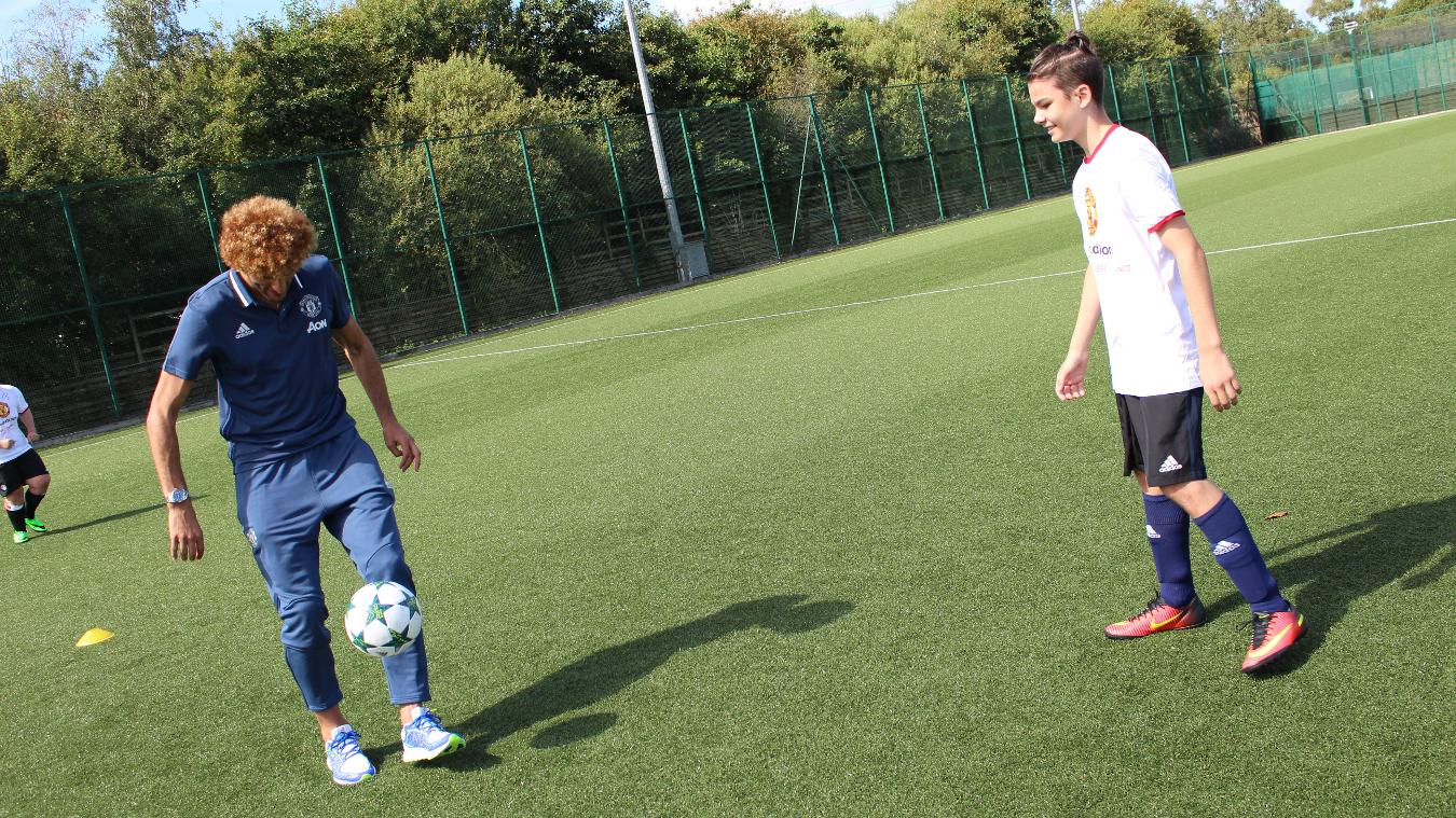 Dylan, 14, from Ability Counts has a keepy-uppy challenge with Marouane Fellaini