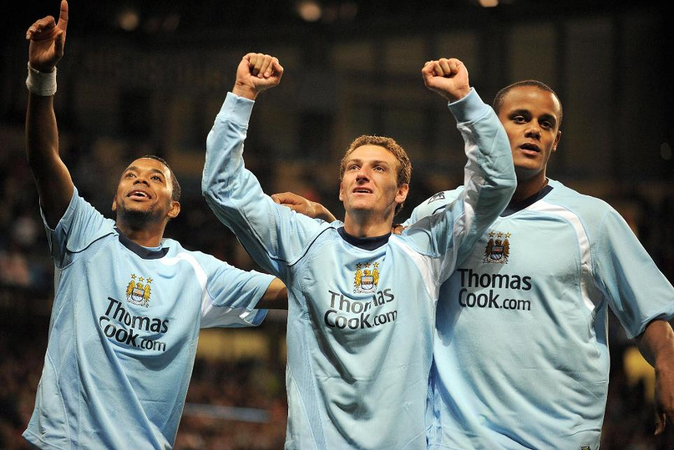 Elano celebrates a goal with Robinho and Vincent Kompany
