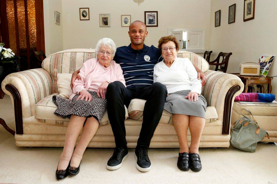 Vincent Kompany with two Manchester City fans