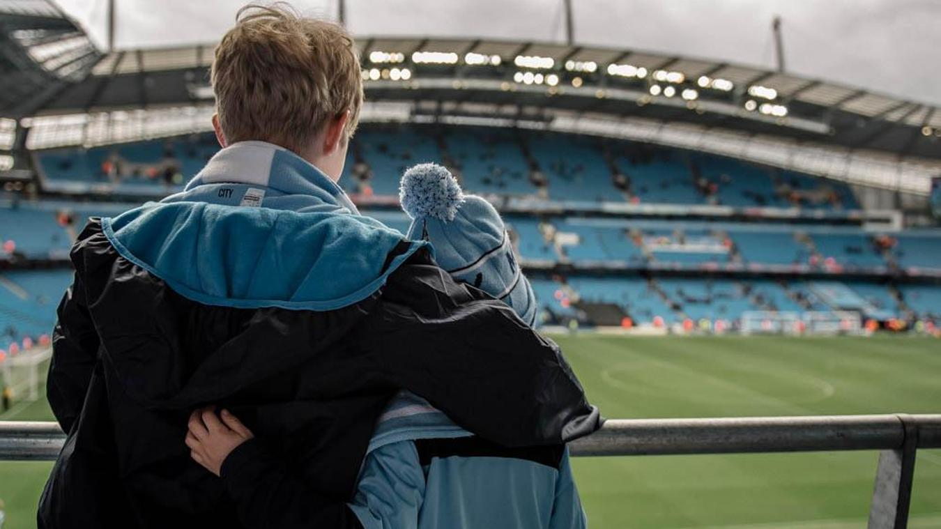 Sam, aged nine, and Toby, who is four embrace at the Etihad Stadium