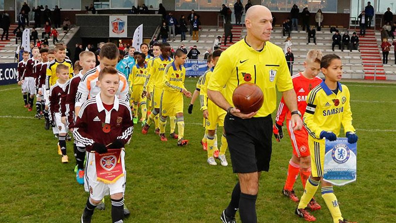 Chelsea and Hearts walk out with Howard Webb for the first match